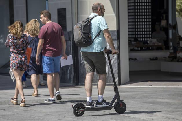 Un usuario de patinete circula por la peatonal Carlos III de Pamplona.