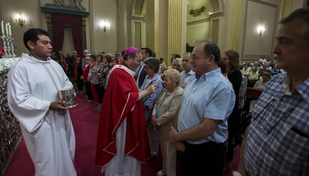El arzobispo Francisco Pérez posa ayer el hisopo con agua bendita en la frente de una nueva cofrade de la Corte de San Fermín.