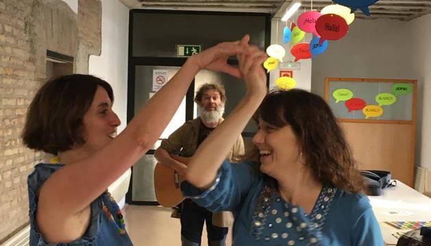 Bob Adamson, profesor de inglés, toca los acordes de un baile típico escocés mientras Gemma Rodríguez (izq.), otra profesora, baila con una futura alumna. Junto a estas líneas, el cuestionario sobre lenguas.