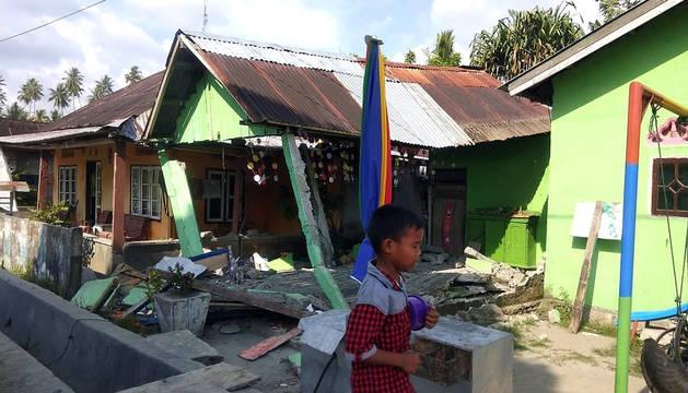 Un niño camina entre los escombros de una casa tras un terremoto de magnitud 7,5 que sacudió la isla de Célebes.