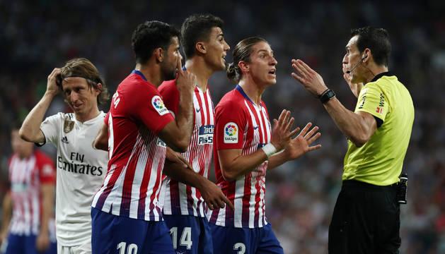 Los jugadores del Atlético reclaman la revisión del VAR a Martínez Munuera, tras una mano de Casemiro dentro del área.