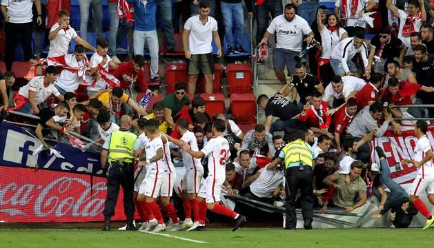 Aficionados del Sevilla caen tras ceder una de las vallas en la celebración del segundo gol del equipo andaluz.