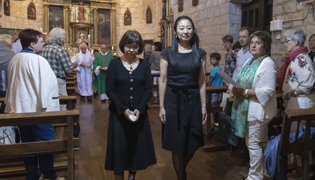 Yuki y su madrina, Keiko, se dirigen a la pila bautismal.