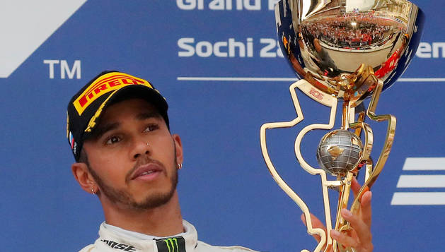 Hamilton celebra su primera posición con el trofeo en brazos.