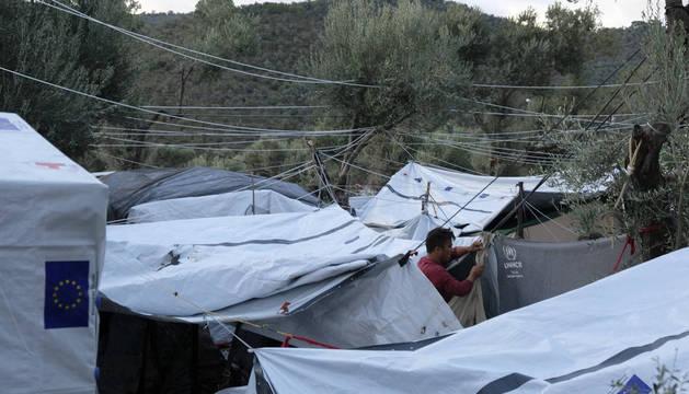 Un refugiado trata de reparar una de las tiendas dañadas por efecto del ciclón Zorba.