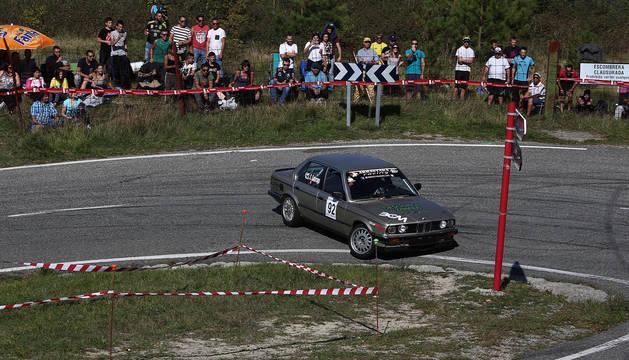 Un BMW, en la edición de 2017 de la Subida a Urbasa, tomando una curva ante la mirada de los aficionados.