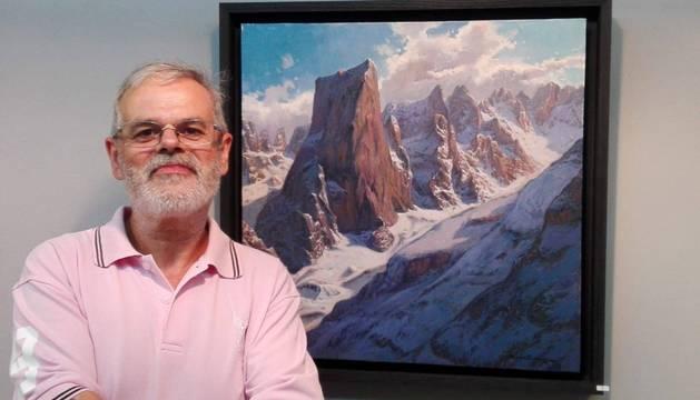 El artista Carlos Sempere posa ante uno de los cuadros de la exposición Viaje por los Picos de Europa.