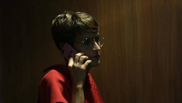 María Chivite habla por teléfono junto a la puerta del salón de plenos del Parlamento.