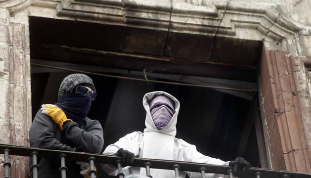 Dos jóvenes con el rostro cubierto, en uno de los balcones del 'gaztetxe Maravillas', en la primera 'okupación' de Rozalejo en 2017.