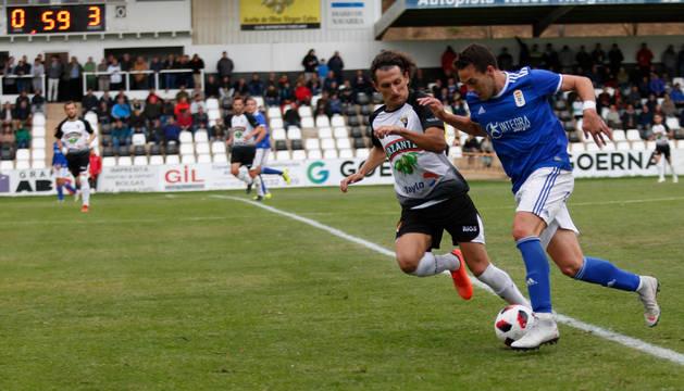 El defensa del Tudelano Álvaro Meseguer intentan evitar el avance de un rival del Oviedo.