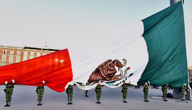 foto de Unos soldados izan la bandera nacional de México.