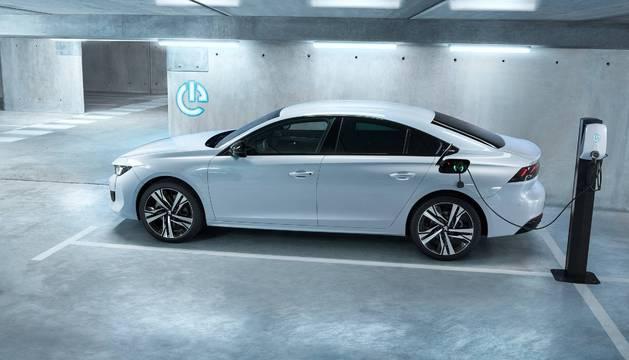 Esta imagen puede ser más habitual de lo que pensamos. El nuevo Peugeot 508 'reposta' electricidad en un poste de recarga. Ofrece además un motor gasolina en modo híbrido, por lo que el conductor no se quedará 'tirado' si se acaba la batería.