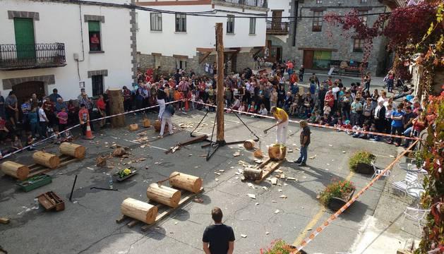 Decenas de personas siguen la prueba de habilidad con hachas matutina en la plaza de Burgui.