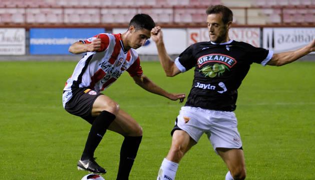 Óscar Vega trata de robar el balón a un jugador de la UD Logroñés, ayer en Las Gaunas.