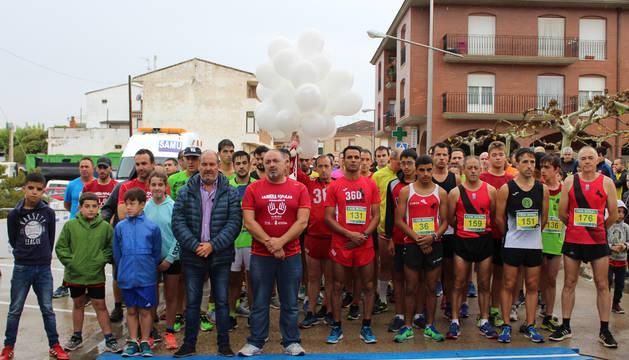 Los corredores junto con los alcaldes de Azagra y Andosilla guardando el minuto de silencio en la salida.