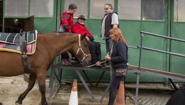 Koldo Manjón se dispone a subir al caballo, ayudado por su mujer. Biki Blasco sujeta al animal.