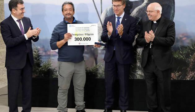 El peregrino madrileño, Manuel Miguel Pozo Guerra (2i), recoge la acreditación de peregrino 300.000 del Camino de Santiago.