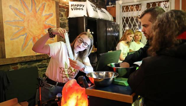 Una mujer enseña a unos clientes el menú de cannabis disponible en la tienda, después de que se aprobara la venta de esta sustancia para fines recreativos en Canadá
