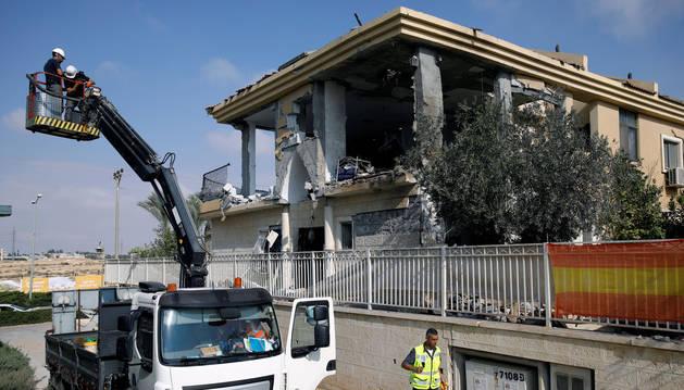 Operarios israelíes trabajan en una casa que fue alcanzada por un cohete disparado desde la Franja de Gaza, según el ejército israelí