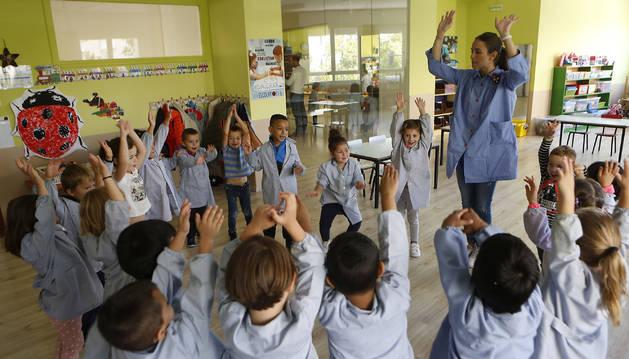 Los alumnos levantan sus manos siguiendo las indicaciones de la profesora.