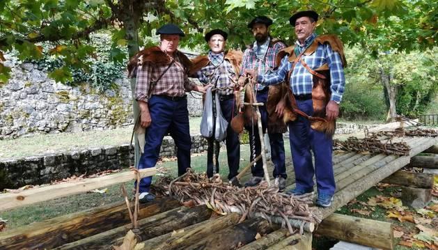 De izda. a dcha., sobre la almadía recreada en Ezcároz, posan vestidos de almadieros Arturo Erlanz, Vitorio Iribarren, César Udi y Mikel Sanz.