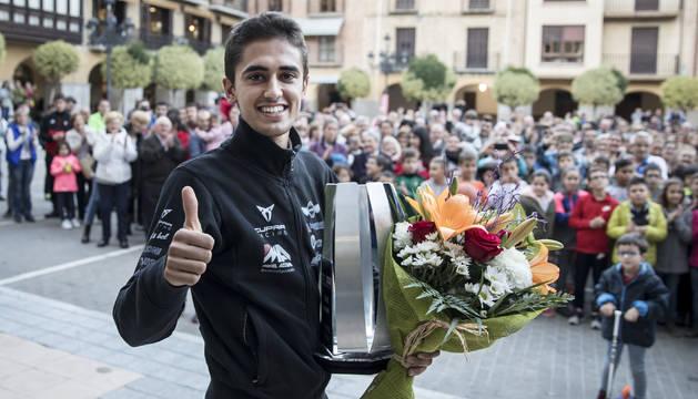 Pulgar en alto de Mikel Azcona, con la plaza del Ayuntamiento de Falces detrás. El navarro sujeta en su mano izquierda el trofeo de campeón de Europa y un ramo de flores.