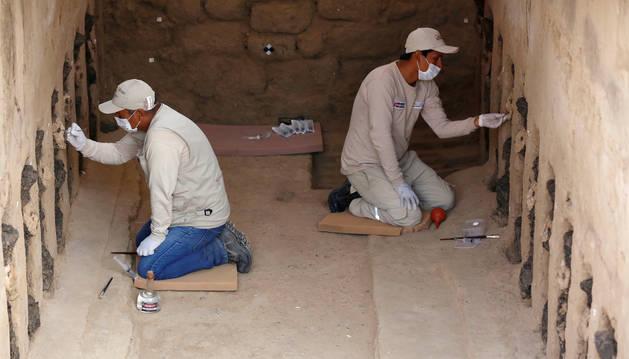 Arqueólogos limpian máscaras de madera de la cultura Mochica en el complejo arqueológico Chan Chan en Trujillo.