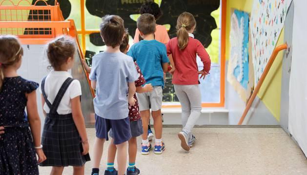 Un grupo de niños y de niñas caminan por los pasillos de un centro escolar.