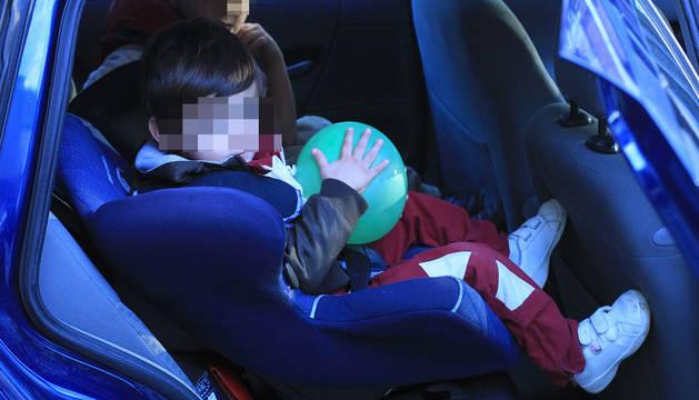 Dos menores, en el asiento de atrás de un coche.