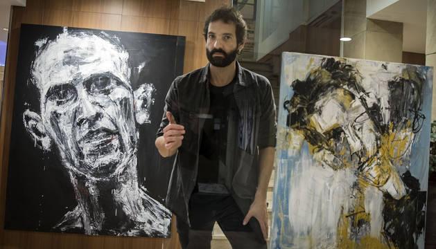 El pintor navarro Fermín Urdánoz, ante dos de las obras que forman parte de la exposición Vacío punto cero instalada en el hotel Maisonnave.