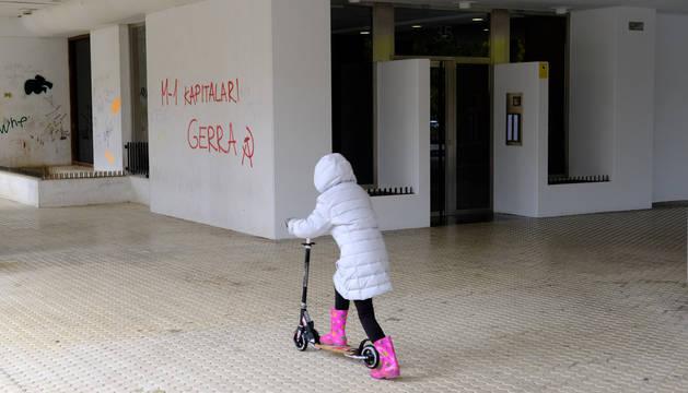 Una niña jugaba este lunes por la mañana con un patinete frente al portal del inmueble donde el sábado desalojaron a 73 estudiantes.