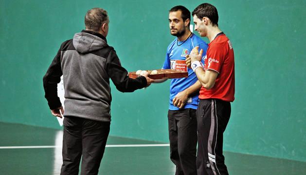 Martín Alústiza ofrece la caja con las pelotas  a Oinatz Bengoetxea y Jokin Altuna tras la elección de material de ayer en el Labrit.