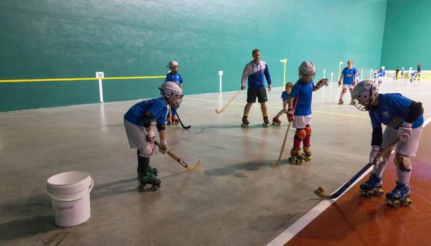 Jugadores del Tudela Hockey Club entrenan en el frontón junto a un cubo que se colocó para evitar que el agua cayera a la pista.