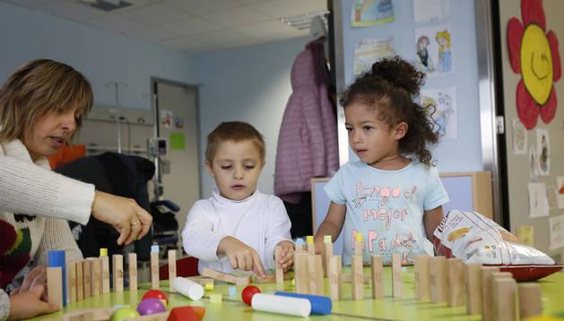 Andrea Fontalba Ramos, en el centro, juega con piezas de madera en el Hospital de Día de Oncología Pediátrica del Complejo Hospitalario de Navarra (CHN).