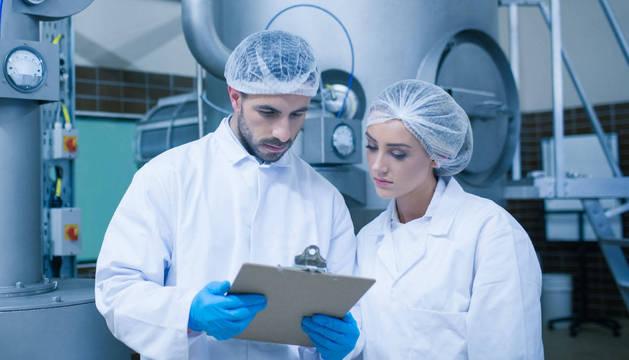 Dos personas miran documentación en una empresa agroalimentaria.