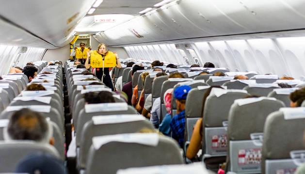 Dos azafatos explican las medidas de seguridad en un avión en una foto de recurso.