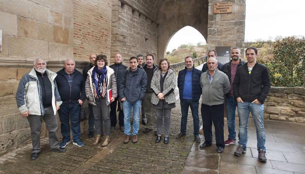Responsables del Departamento, con la consejera Elizalde a la cabeza, con representantes de ayuntamientos de la zona en el acceso sur al puente medieval de Puente la Reina.