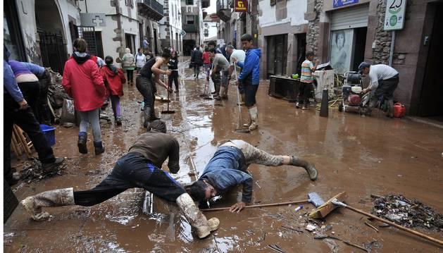 Imagen de la implicación vecinal y de comerciantes en la limpieza de la inundación de Elizondo.