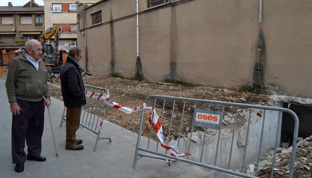 Dos vecinos contemplando el túnel que han dejado al descubierto las obras en el centro de San Adrián.