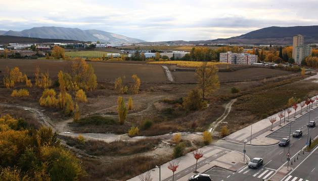 En estos terrenos de Lezkairu, junto a la calle Adela Bazo, se construirá el colegio Paderborn/Víctor Pradera. Al fondo a la derecha, la residencia universitaria de la UPNA y las torres de Arrosadía.