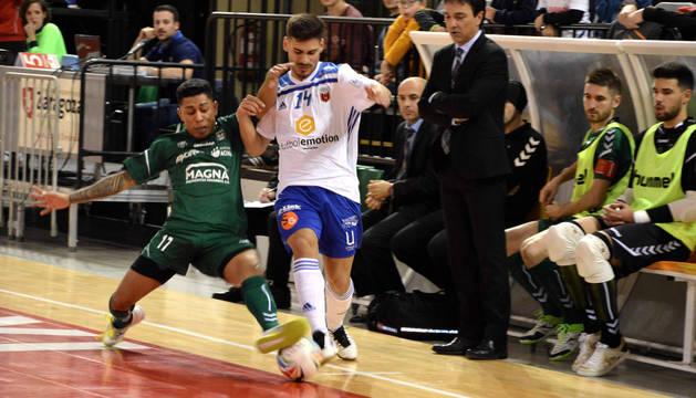 El ala brasileño de Osasuna Magna Bynho trata de frenar a Esteban, del Fútbol Emotion Zaragoza, junto al banquillo navarro.