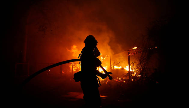 Foto de un bombero lucha contra el fuego en Malibú.