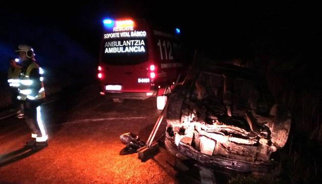 Bomberos en el lugar del accidente, con el coche volcado.