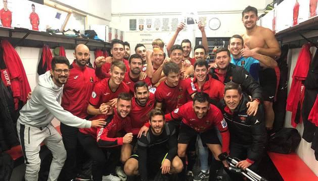 Los jugadores y el cuerpo técnico del Cortes celebraron, en el vestuario, la victoria ante Osasuna Promesas. El goleador Raúl Chueca aparece detrás con los brazos en alto.