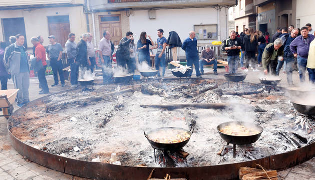 Un grupo de vecinos observa cómo se van cocinando los ranchos en la plaza de los Fueros.