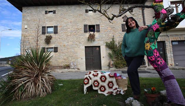 Txaro Sorbet delante de su casa, junto a uno de los árboles que ha forrado con ganchillo.