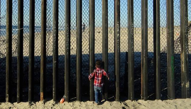 Un niño de la 'caravana migrante' se acerca al muro que separa México de Estados Unidos en Tijuana.