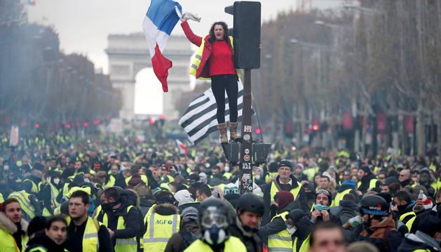 Una manifestante con la bandera de Francia se alza entre una multitud de 'chalecos amarillos' en los Campos Elíseos.