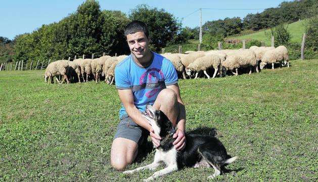 Julen Arburua Jiménez, con uno de sus perros, y parte de su rebaño, en Lekaroz.