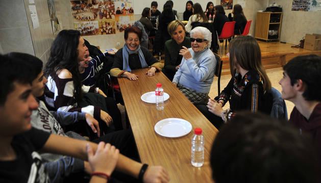 Josefina Añón e Iluminada López, al fondo de la imagen, cuentan sus vivencias a los alumnos de Escolapios.